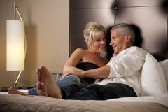 Homme et femme détendant dans un bâti de chambre d'hôtel Images stock