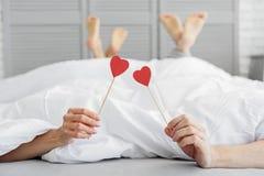 Homme et femme détendant ensemble dans la chambre à coucher Image stock