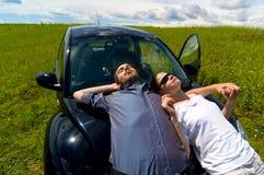 Homme et femme détendant sur un véhicule Photo libre de droits