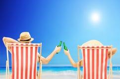 Homme et femme détendant sur une plage et encourageant avec des bières image stock