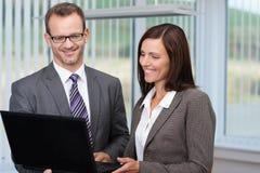 Homme et femme d'affaires à l'aide d'un ordinateur portable image stock