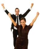 Homme et femme d'affaires avec des bras en air Photographie stock libre de droits