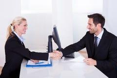 Homme et femme d'affaires se serrant la main Photo stock