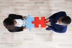 Homme et femme d'affaires tenant des morceaux de puzzle Photographie stock