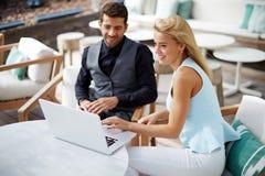 Homme et femme d'affaires travaillant ensemble sur un ordinateur portable en café moderne image stock