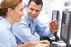 Homme et femme d'affaires travaillant sur des ordinateurs Photographie stock libre de droits
