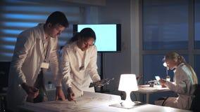 Homme et femme dans des manteaux de laboratoire fonctionnant dans le laboratoire d'électronique avec le plan de circuits de carte banque de vidéos