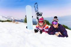 Homme et femme dans des masques de ski se trouvant sur la neige Images stock