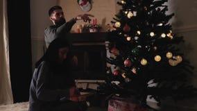 Homme et femme dans l'amour décorant l'arbre de Noël à la maison La femme corrige l'arc sur le boîte-cadeau Les couples heureux s banque de vidéos