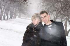 Homme et femme dans l'amour dans la tempête de neige Image stock