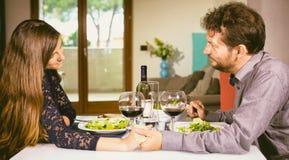 Homme et femme dans l'amour tenant la main regardant dans les yeux la table à la maison Images stock