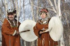 Homme et femme dans la robe nationale de Koryak avec des tambours de basque Photographie stock libre de droits