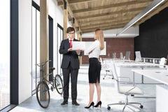 Homme et femme dans le bureau avec une affiche et un vélo Photographie stock libre de droits