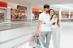 Homme et femme dans le centre commercial Le couple étreint images stock