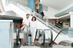 Homme et femme dans le centre commercial Le couple monte sur l'escalator image libre de droits