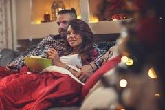 Homme et femme dans le lit regardant la TV et mangeant du maïs de bruit Photographie stock