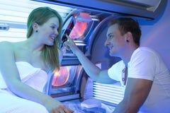 Homme et femme dans le salon de bronzage au lit pliant photos libres de droits