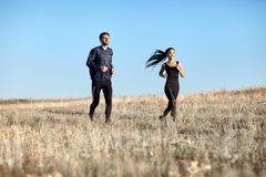 Homme et femme dans les vêtements de sport fonctionnant dans le domaine Image libre de droits