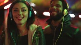 Homme et femme dansant au rythme de la musique avec des écouteurs banque de vidéos