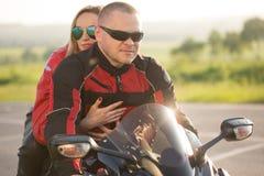 Homme et femme de motard s'asseyant sur une moto Photographie stock libre de droits