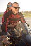Homme et femme de motard s'asseyant sur une moto Photo stock