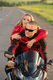 Homme et femme de motard s'asseyant sur une moto Photographie stock