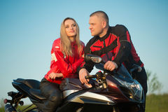 Homme et femme de motard s'asseyant sur une moto Image stock