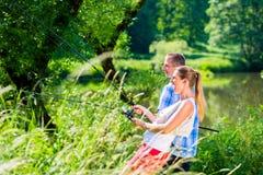 Homme et femme de pêche ainsi que la tige à la rivière Image libre de droits