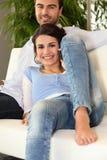 Homme et femme de sourire au téléphone sur un sofa Photos libres de droits