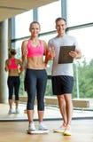 Homme et femme de sourire avec des échelles dans le gymnase Photos stock