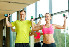 Homme et femme de sourire avec des haltères dans le gymnase Photos stock