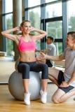 Homme et femme de sourire avec la boule d'exercice dans le gymnase Photographie stock