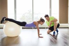 Homme et femme de sourire avec la boule d'exercice dans le gymnase Image libre de droits