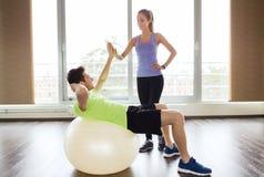 Homme et femme de sourire avec la boule d'exercice dans le gymnase Photos stock