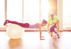 Homme et femme de sourire avec la boule d'exercice dans le gymnase Photo libre de droits