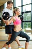 Homme et femme de sourire avec le barbell dans le gymnase Photo stock