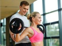 Homme et femme de sourire avec le barbell dans le gymnase Photos stock