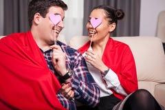 Homme et femme de sourire couverts de couverture rouge Photographie stock