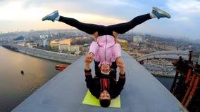 Homme et femme de sourire faisant des cascades acrobatiques de yoga sur le pont, drogués d'adrénaline photographie stock libre de droits