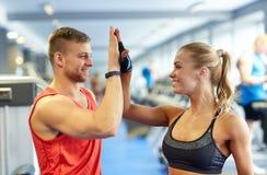 Homme et femme de sourire faisant la haute cinq dans le gymnase Images stock
