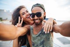 Homme et femme de sourire faisant la photo de selfie sur le smartphone Photo stock