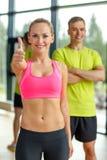 Homme et femme de sourire montrant des pouces dans le gymnase Photo libre de droits