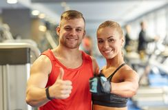 Homme et femme de sourire montrant des pouces dans le gymnase Photographie stock