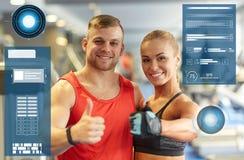 Homme et femme de sourire montrant des pouces dans le gymnase Photo stock