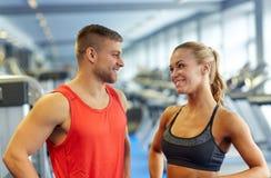 Homme et femme de sourire parlant dans le gymnase Photos stock