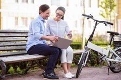 Homme et femme de sourire parlant en parc avec un ordinateur portable Photo stock