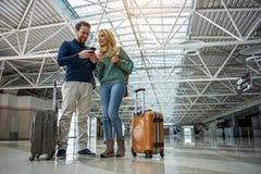 Homme et femme de sourire payant la carte d'embarquement Image libre de droits