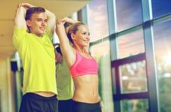 Homme et femme de sourire s'exerçant dans le gymnase Photos stock
