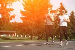 Homme et femme de sport pulsant en parc Image stock