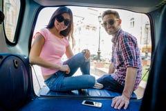 Homme et femme de touristes heureux dans la voiture Photographie stock libre de droits